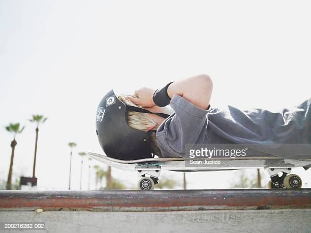 Boy (10-12) laying on skateboard with hand on head