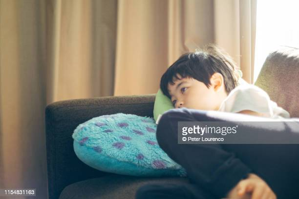 boy laying on sofa - peter lourenco stock pictures, royalty-free photos & images