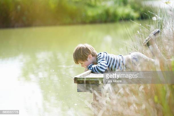 Boy laying on wood dock looking at river in nature