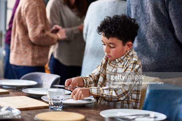 boy laying table at extended family meal - photography stock pictures, royalty-free photos & images