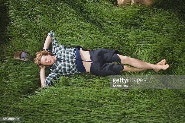 a boy lays down on the green grass, houten, the netherlands - lying down stock-fotos und bilder