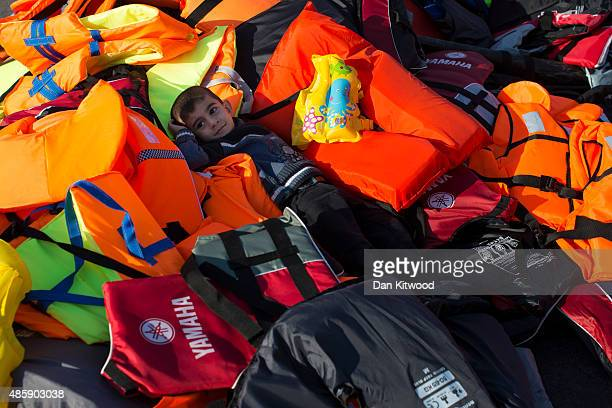 A boy lays in a pile of life jackets on at the ferry port on August 30 2015 in Kos Greece Migrants from many parts of the Middle East and African...