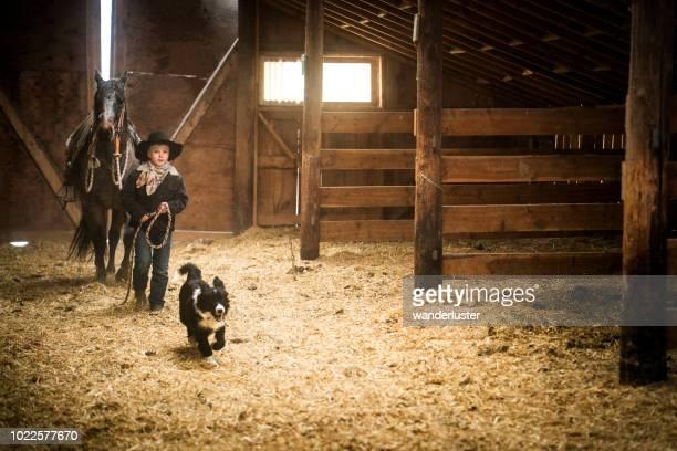 Boy leading horse in barn