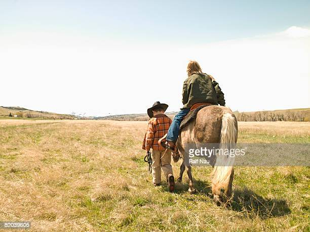 Boy leading pony while girl rides