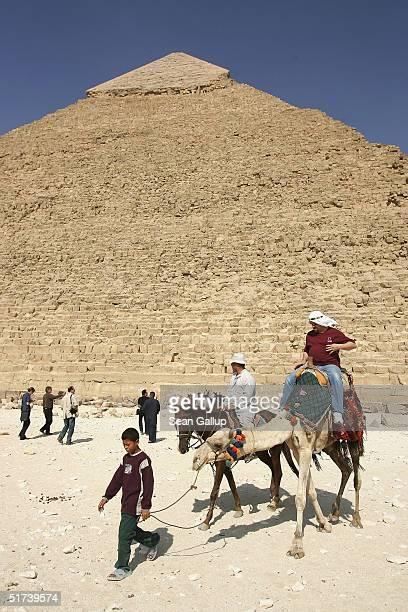 A boy leads tourists on horseback and camel past Khafre pyramid November 13 2004 at Giza just outside Cairo Egypt The three large pyramids at Giza...