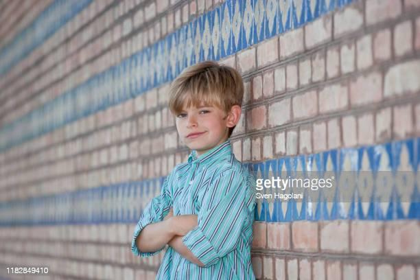 a boy leaning against a wall and smirking - menino loiro olhos azuis imagens e fotografias de stock