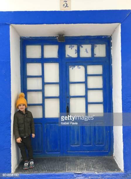 Boy leaning against blue door