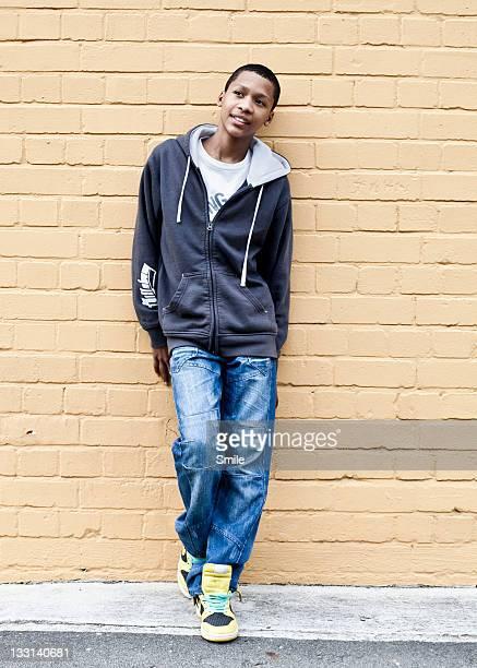 Boy leaning against brick wall
