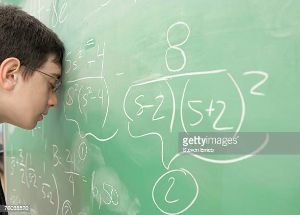 boy (11-13 years) leaning against chalkboard, side view - 12 13 years stock pictures, royalty-free photos & images