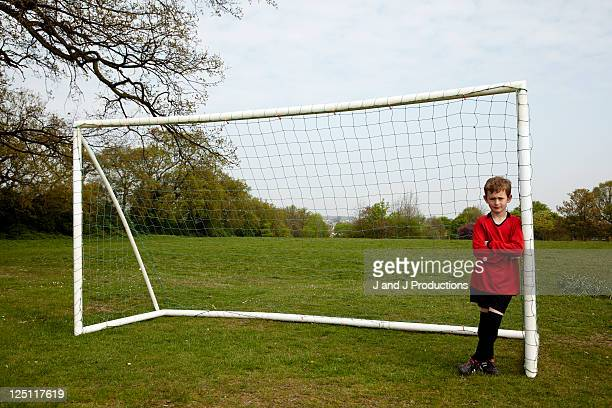 boy leaning against football post - goalkeeper stock pictures, royalty-free photos & images