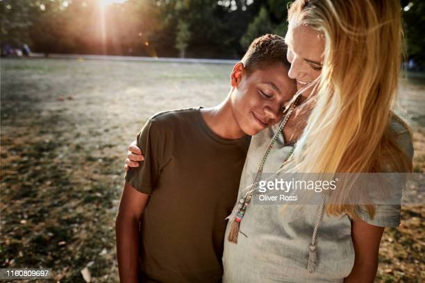 boy leaning against pregnant mother's shoulder in a park - son stock pictures, royalty-free photos & images