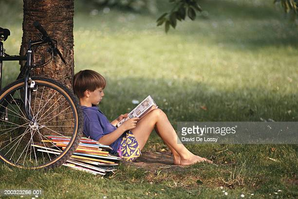Boy (10-11) leaning against tree, reading book, side view