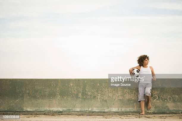 Boy fuertemente contra la pared con de fútbol