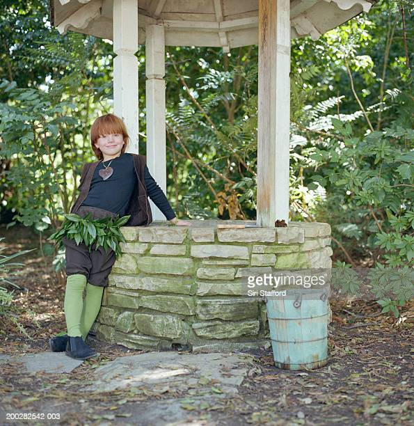 Boy (6-8) leaning against wishing well