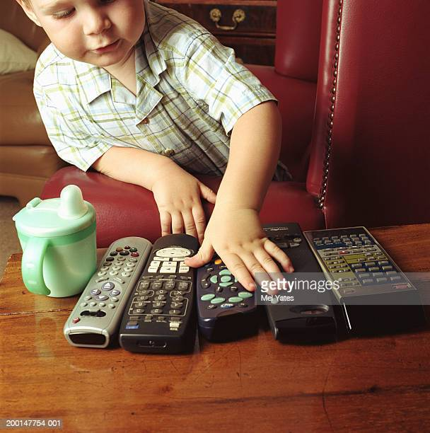 boy (2-4) leaning on arm of leather chair, hand on remote control - medium group of objects stock pictures, royalty-free photos & images
