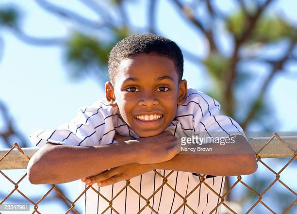 Boy (12-13) leaning on fence, portrait