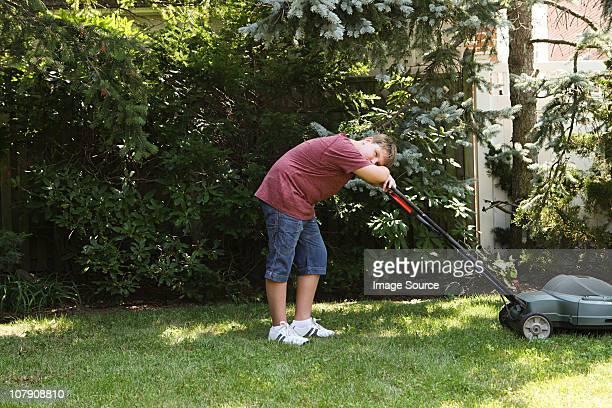 Boy leaning on lawnmower