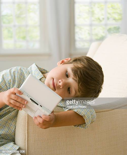 boy (6-7) leaning on sofa, playing video game - handheld video game stock pictures, royalty-free photos & images