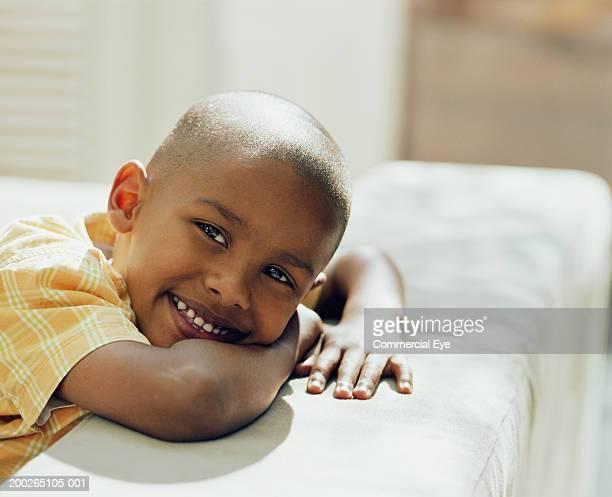 Boy (5-7) leaning on sofa, portrait, close-up
