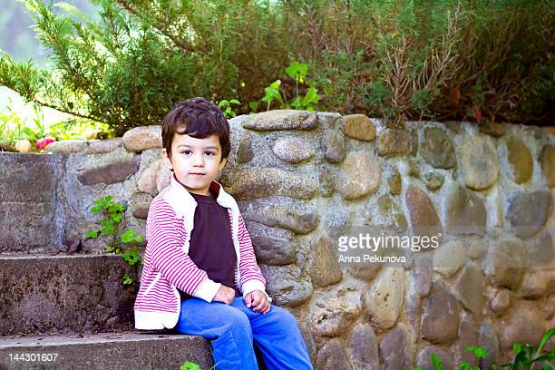 Boy leaning on stone wall