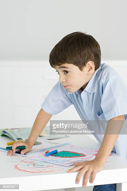 Boy leaning on table, holding crayon, colorful drawing on paper and the table