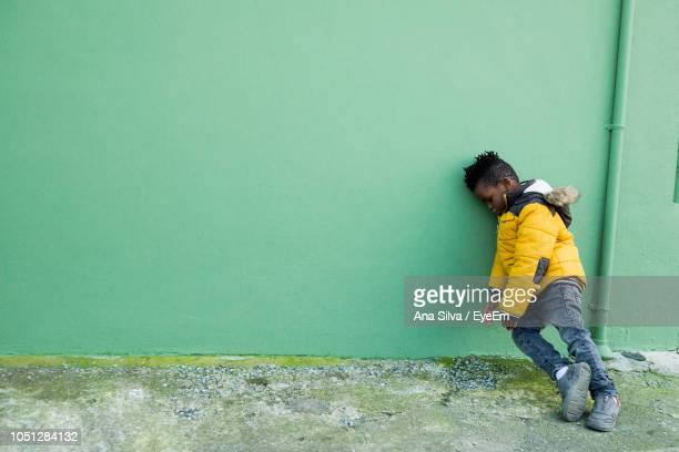 Boy Leaning On Yellow Wall