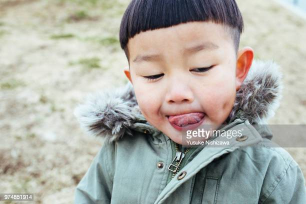 a boy leaning out a tongue - yusuke nishizawa stock pictures, royalty-free photos & images