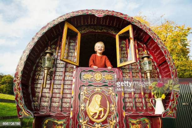 a boy leaning out of the open shutters at the rear of a bow top gypsy caravan. - gypsy caravan stock pictures, royalty-free photos & images