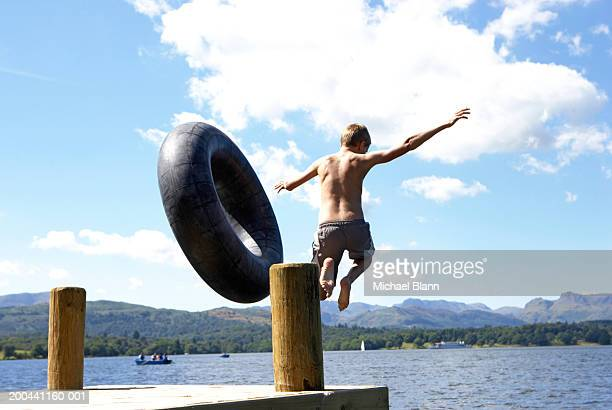 Boy (11-13) leaping from lake jetty with rubber ring, rear view