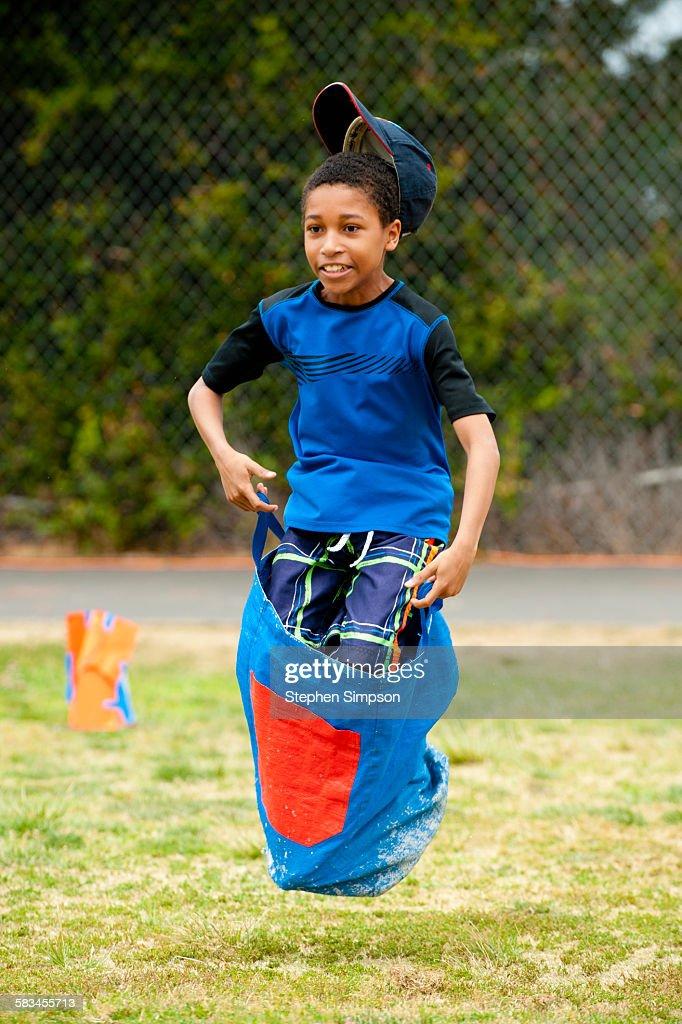 boy leaping in school sack race : Stock Photo