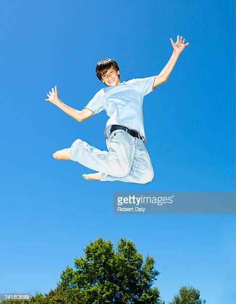 Junge springen im Freien mit blauen Himmel und Bäume