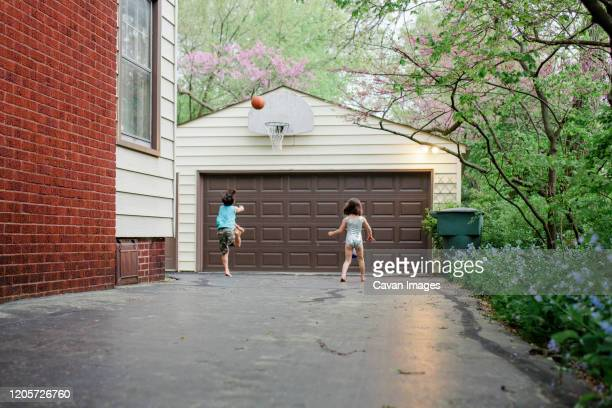 a boy leaps to shoot a basketball in driveway while sister watches on - driveway stock pictures, royalty-free photos & images
