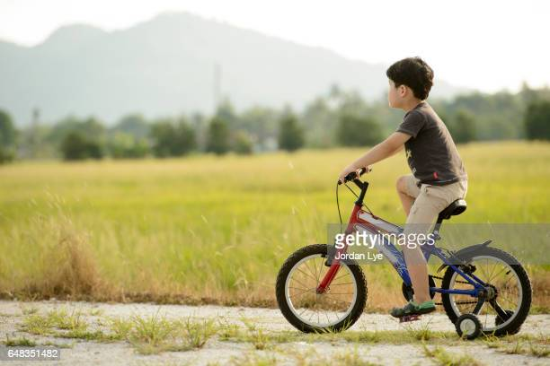 Boy learn cycling in country road