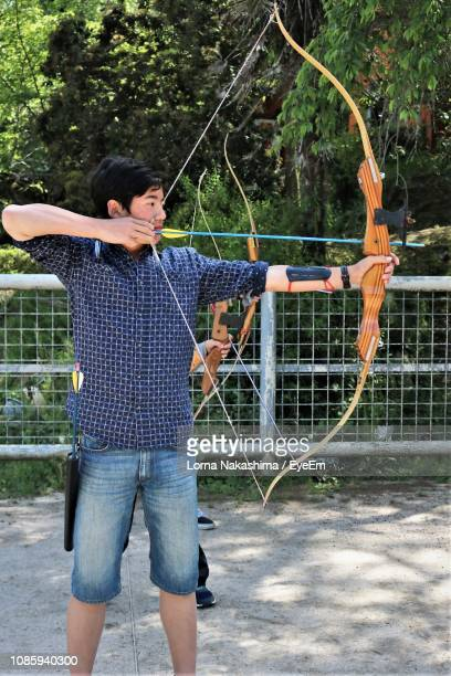 boy learning archery - bow and arrow stock pictures, royalty-free photos & images