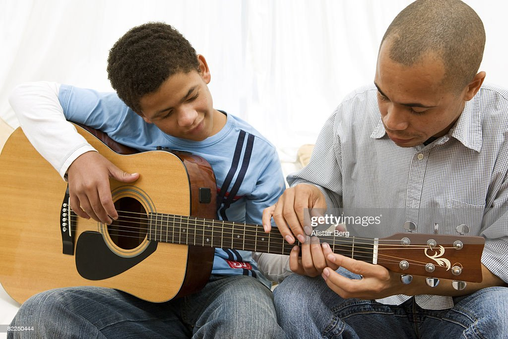 Boy learning guitar with his dad : Stock Photo