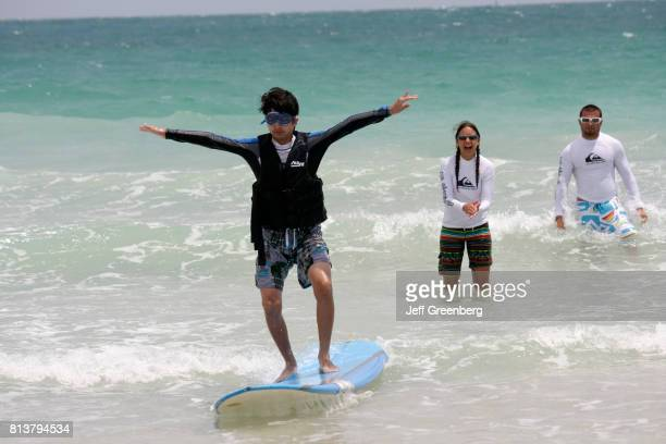 A boy learning how to surf at the Recreation Department Surf Camp