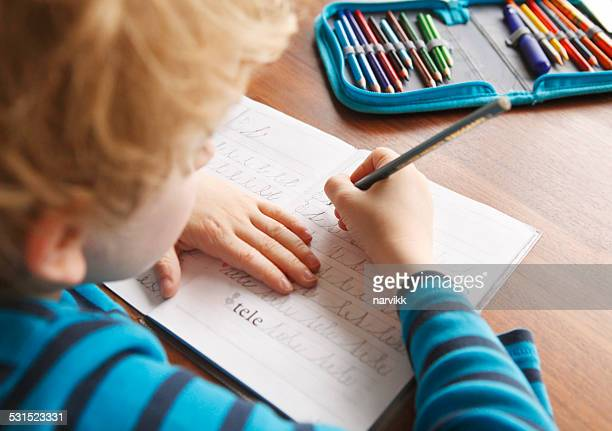 boy learning to write alphabet characters - writing stock pictures, royalty-free photos & images