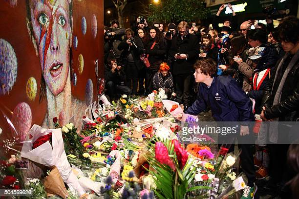 A boy leaves flowers beneath a mural of David Bowie in Brixton on January 11 2016 in London England British music and fashion icon David Bowie died...
