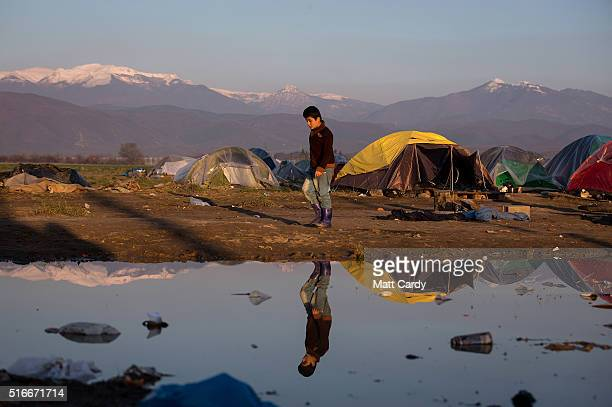 A boy leaves his tent as the sun rises at the Idomeni refugee camp on the Greek Macedonia border on March 20 2016 in Idomeni Greece Thousands of...
