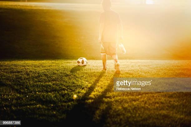 boy leaving soccer field, walking into sunset