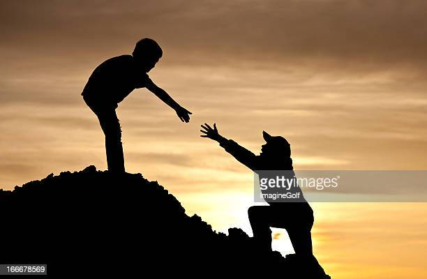 Boy Lending A Helping Hand to Friend Climbing