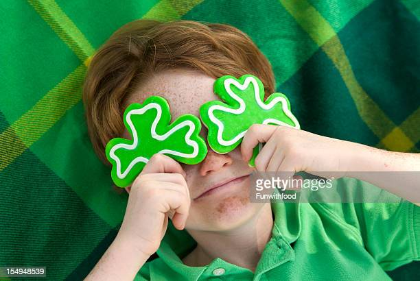 boy leprechaun, smiling irish child & st. patrick's day shamrock cookies - st patricks day stock pictures, royalty-free photos & images