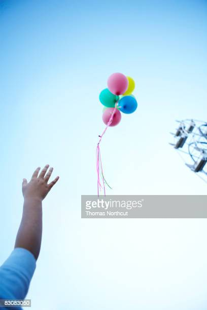 boy letting go of balloons  - releasing stock pictures, royalty-free photos & images