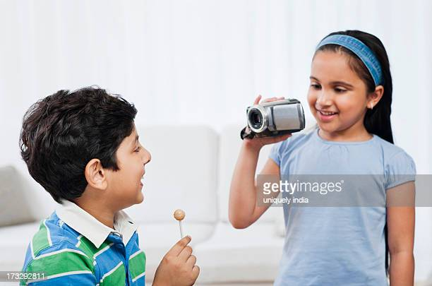 Boy licking a lollipop and his sister filming him with a video camera