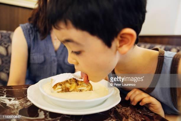 boy licking apple strudel - peter lourenco - fotografias e filmes do acervo