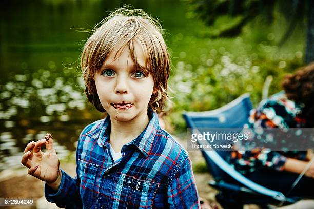 Boy licking chocolate off of lips while camping