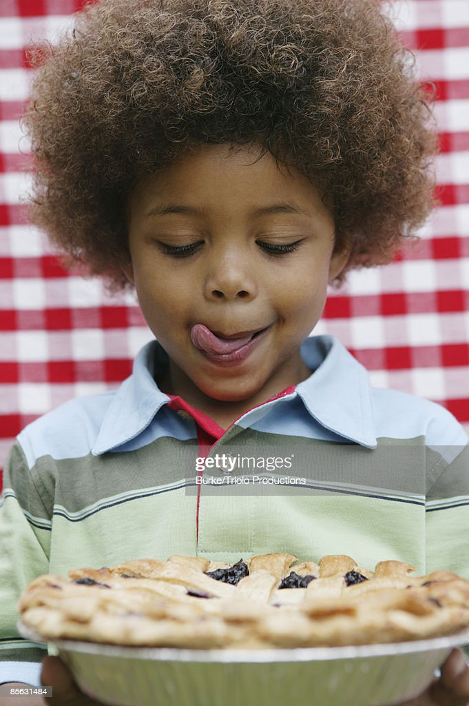 Boy licking lips at pie : Stock Photo