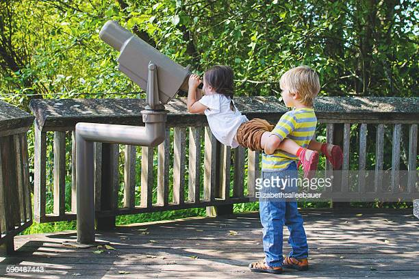 Boy lifting girl to look through telescope