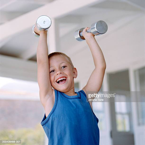 Boy (3-5) lifting hand weights above head, smiling