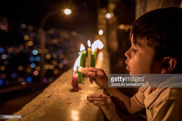 A boy light candles during the Day of the Little Candles celebrations in Medellin Colombia on December 7 2018 The Day of the Little Candles is a...